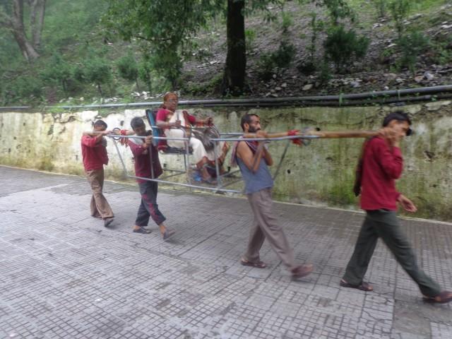 वैष्णो देवी यात्रा मार्ग पर पालकी में जाती एक महिला यात्री