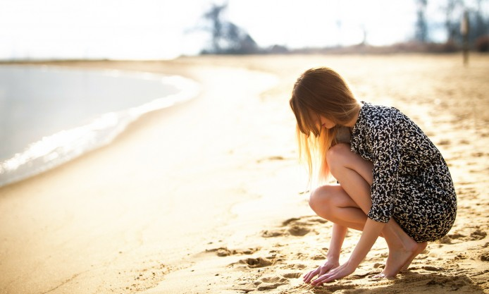 a-girl-sitting-alone-on-a-sandy-beach-at-sunset-694x417