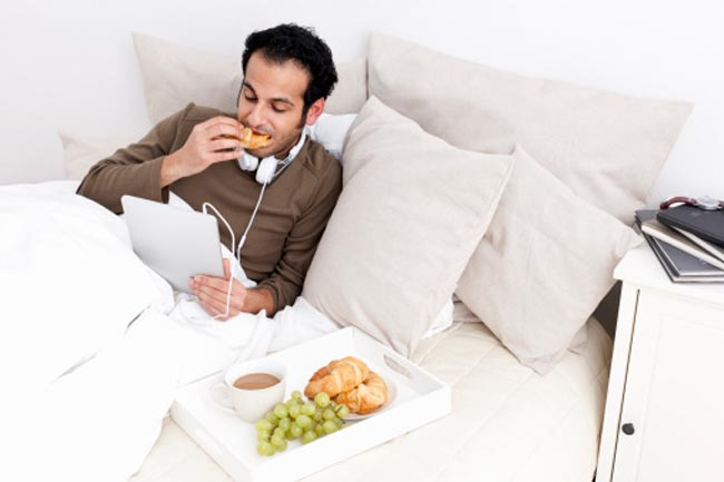 Man with tablet computer eating in bed