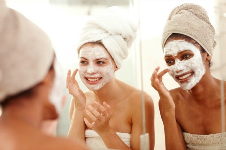 Diverse friends smiling while applying skincare face masks to their faces