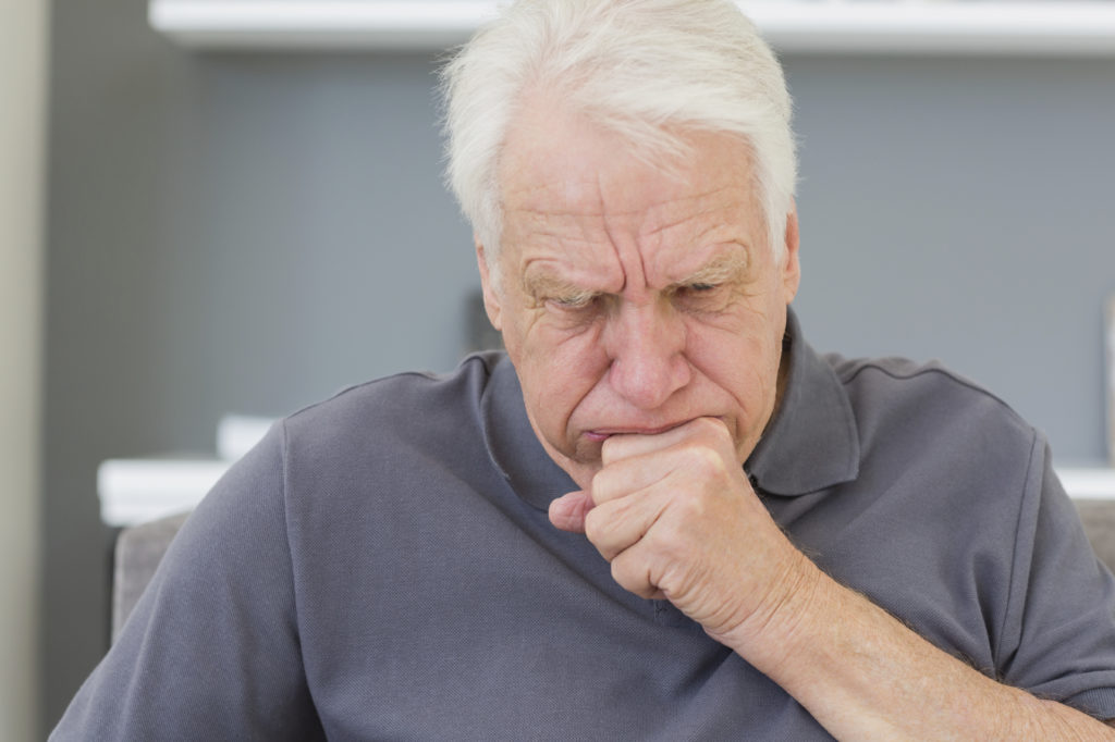 Mature man sitting on sofa coughing at his home
