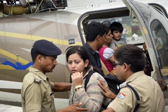 तबाही के बाद आपदा पीड़ितों को हेलिकॉप्टर में बैठाते पुलिसकर्मी