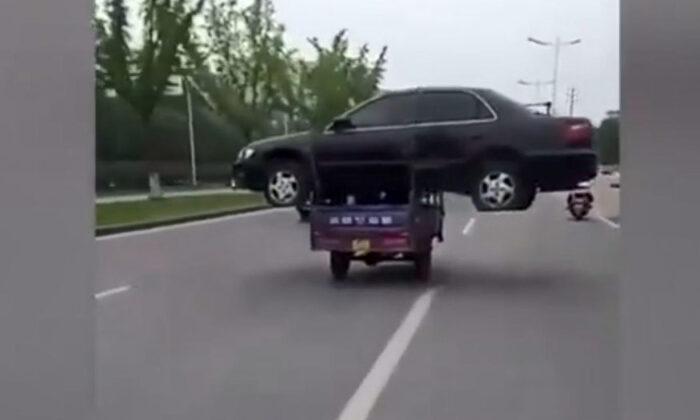 three wheeler auto carries four wheeler car